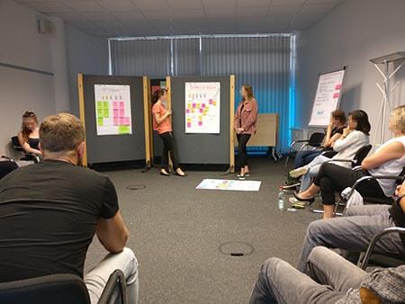 Mehrere Personen sitzen in einem Stuhlkreis und hören zwei Frauen zu, die an einer Mateplanwand stehen und offenbar eine Präsentation halten.