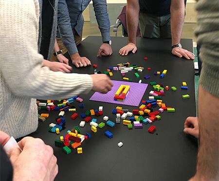 Mehrere Personen stehen um einen Tisch herum und bauen ein Modell aus Lego-Steinen.