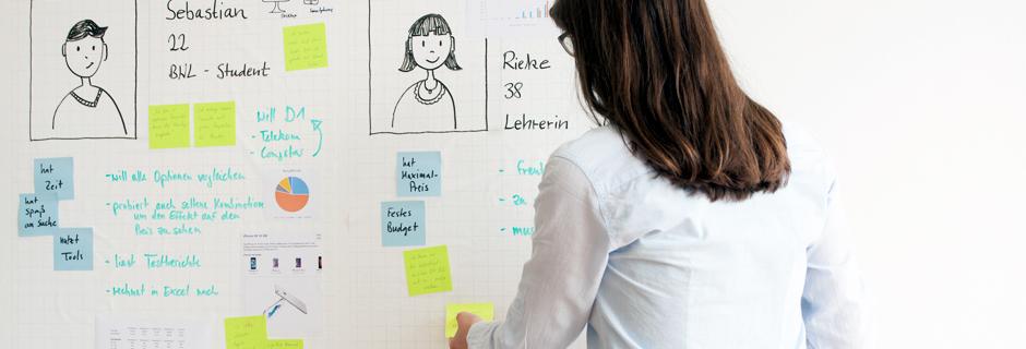 Person steht vor einem Whiteboard und haftet einen Post-It an.
