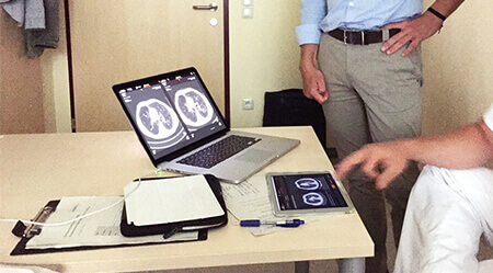 A radiologist sits at table and tests the prototype at a tablet and a laptop