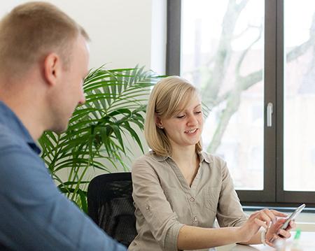 Zwei Personen sitzen an einem Tisch. Eine von ihnen bedient ein Smartphone, die andere schaut ihr zu.