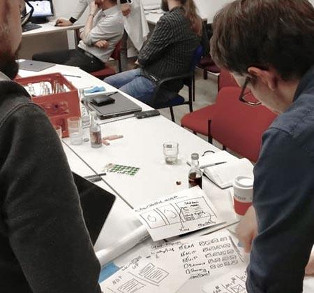 Zwei Personen beugen sich über handgezeichnete Skizzen.
