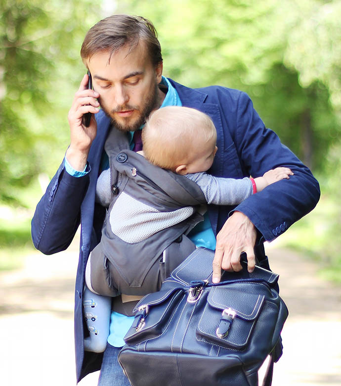 Phoning man carrying a child.