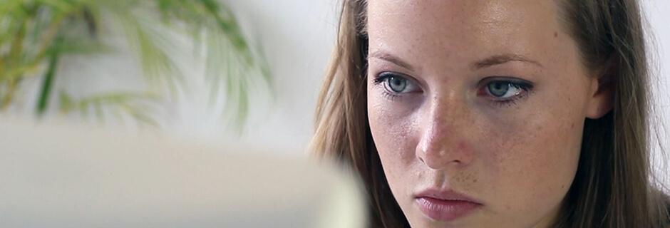 Junge Frau schaut konzentriert auf einen Bildschirm
