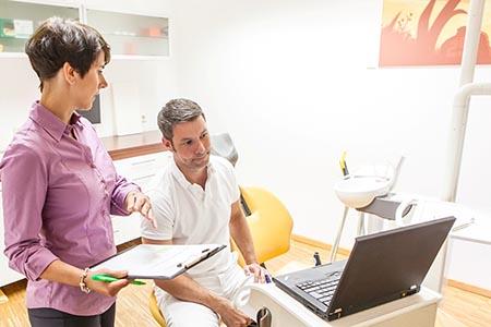 Zwei Personen schauen gemeinsam auf einen Laptop. Eine von ihnen hält ein Klemmbrett in der Hand, die andere ist in weiß gekleidet (Arzt).