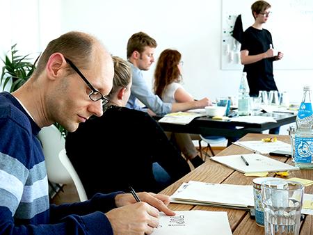 Mehrere Personen in einer Seminar-Situation.