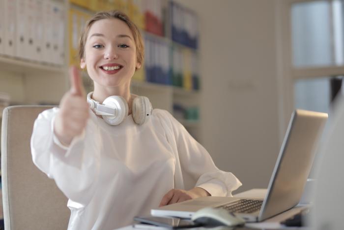 """Eine Frau sitzt vor dem Rechner und gibt lächelnd ein """"Daumen hoch"""""""