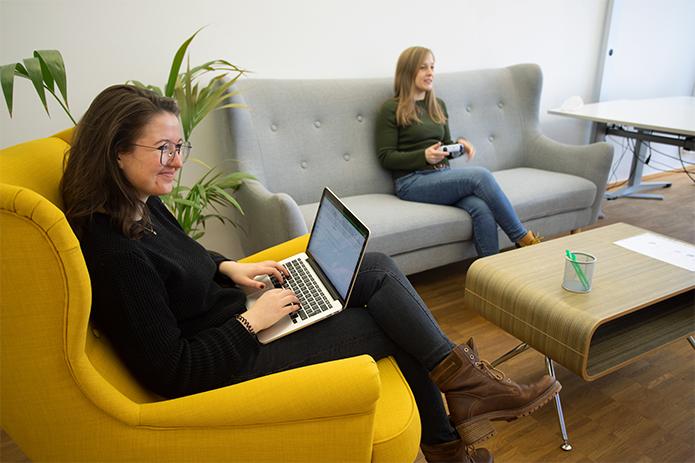 Praktikantin Inken beobachtet eine Usability-Test-Teilnehmerin bei der Benutzung einer Spielekonsole und macht Notizen auf ihrem Laptop.